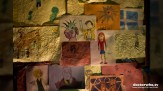 A wall of art featuring the Doctor and some of his friends and foes in The Time of the Doctor