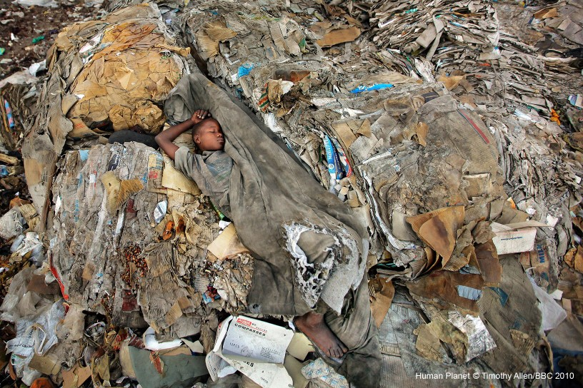 Mombasa, Kenya. A child sleeps on the vast urban rubbish dump where he lives.